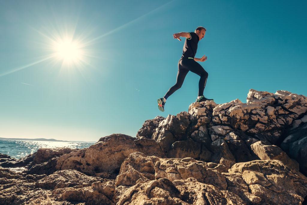 Man runs on rocky sea side