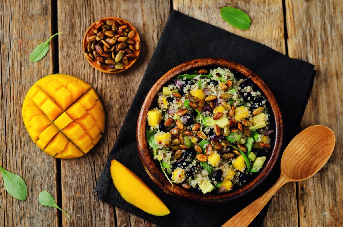 Mango black bean arugula pumpkin seed quinoa salad. toning. selective focus